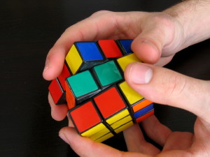Two hands manipulating a Rubik's Cube