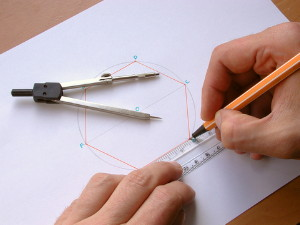 Two hands constructing a regular hexagon with pair of compasses and straight edge